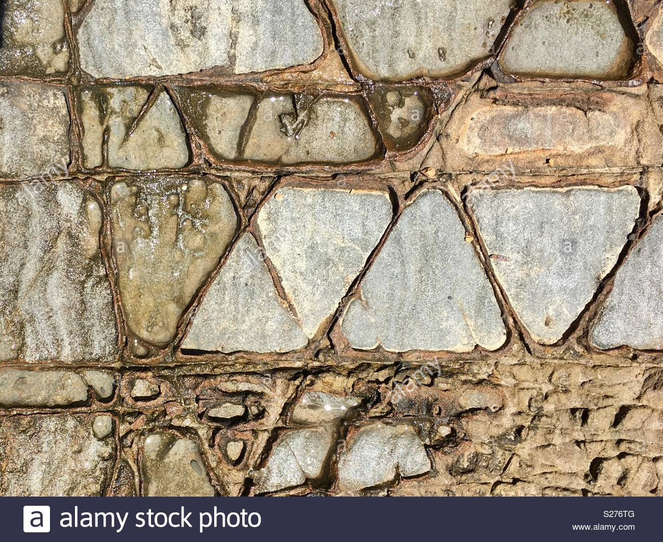 Geometric tidal rocks weathered by the sea - Stock Image