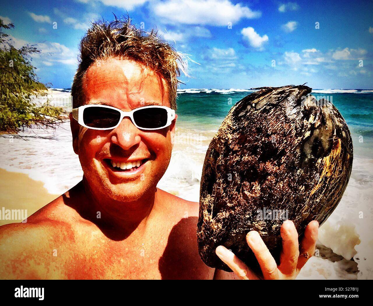 Gleeful tanned smiling man with white sunglasses beholds the coconut gift from the sea - Stock Image