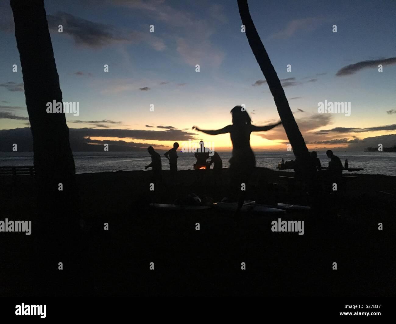 Friends, Sunset, slack line balancing, fire, fish tacos for dinner, full moon surf! Summertime in Maui!!! - Stock Image