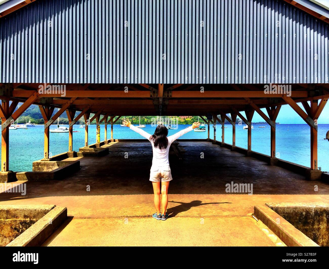 Young woman, long brunette hair and shorts, arms outstretched in yoga pose at the end of Hanalei Bay pier in Northshore Kauai - Stock Image