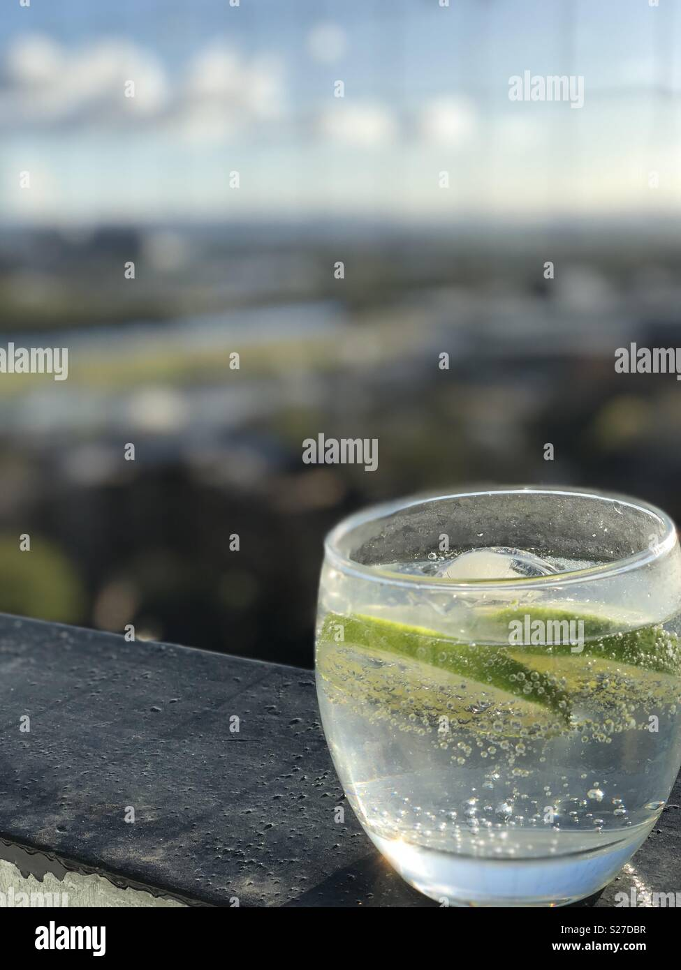 Gin with tonic and lime on a Balcony in Glasgow on a summer evening - Stock Image