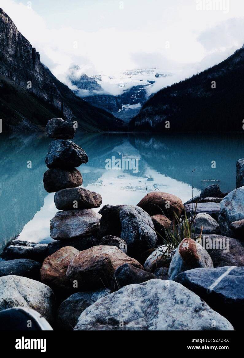 Stacked inukshuk rocks at Lake Louise with snowy peaks in the background - Stock Image