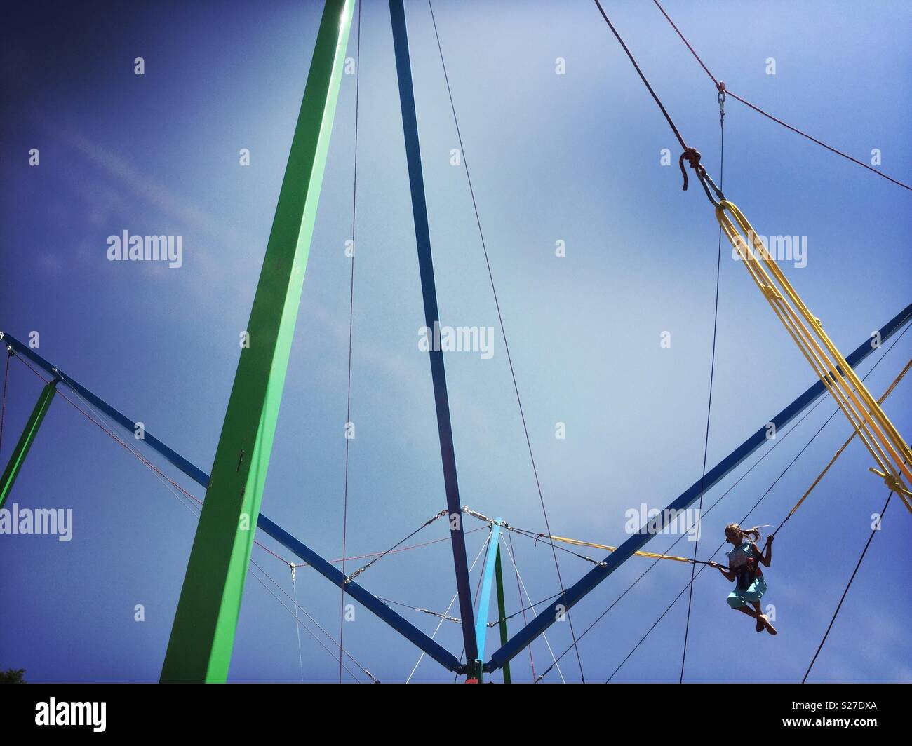 A girl bounces on a trampoline attached to bungee cords in a fairground in Sochi, Russia. - Stock Image