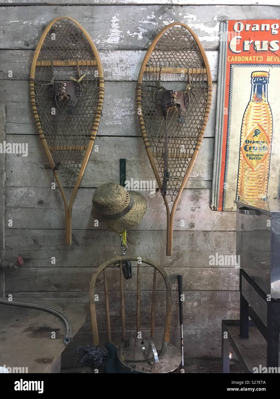 Still life in a barn, yesteryear, snow shoes & vintage drink advert Stock Photo