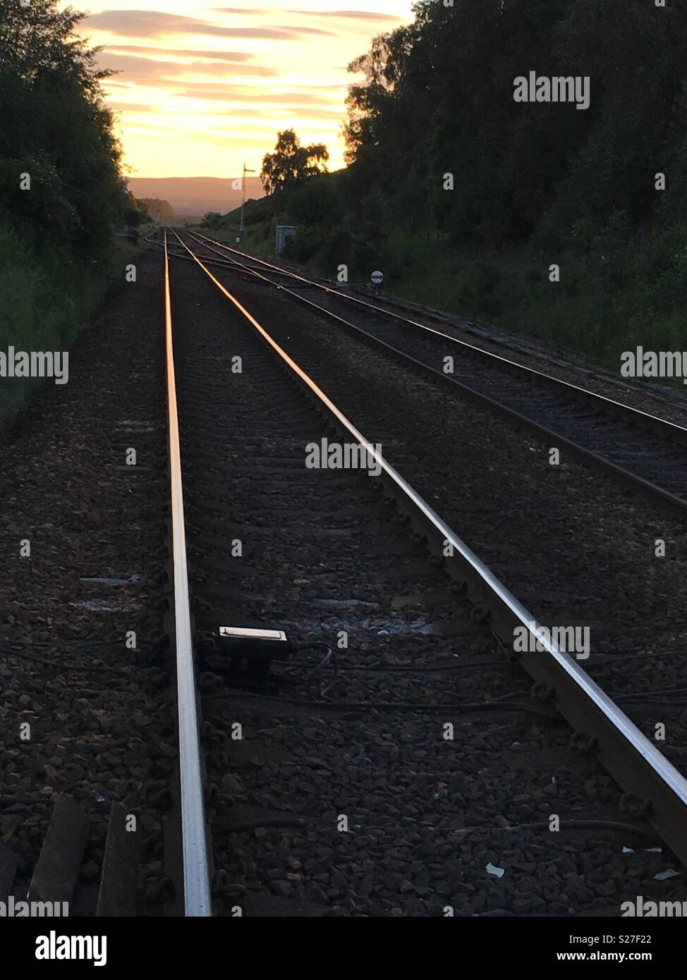 Train tracks running into the distance at sunset, Scotland, UK - Stock Image