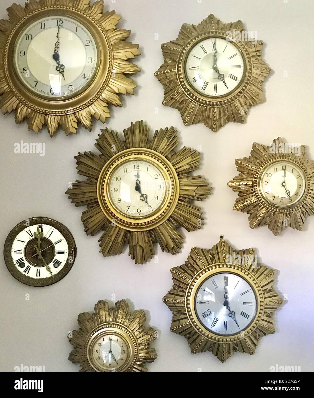 Collection of gold wall clocks in sunburst style - Stock Image