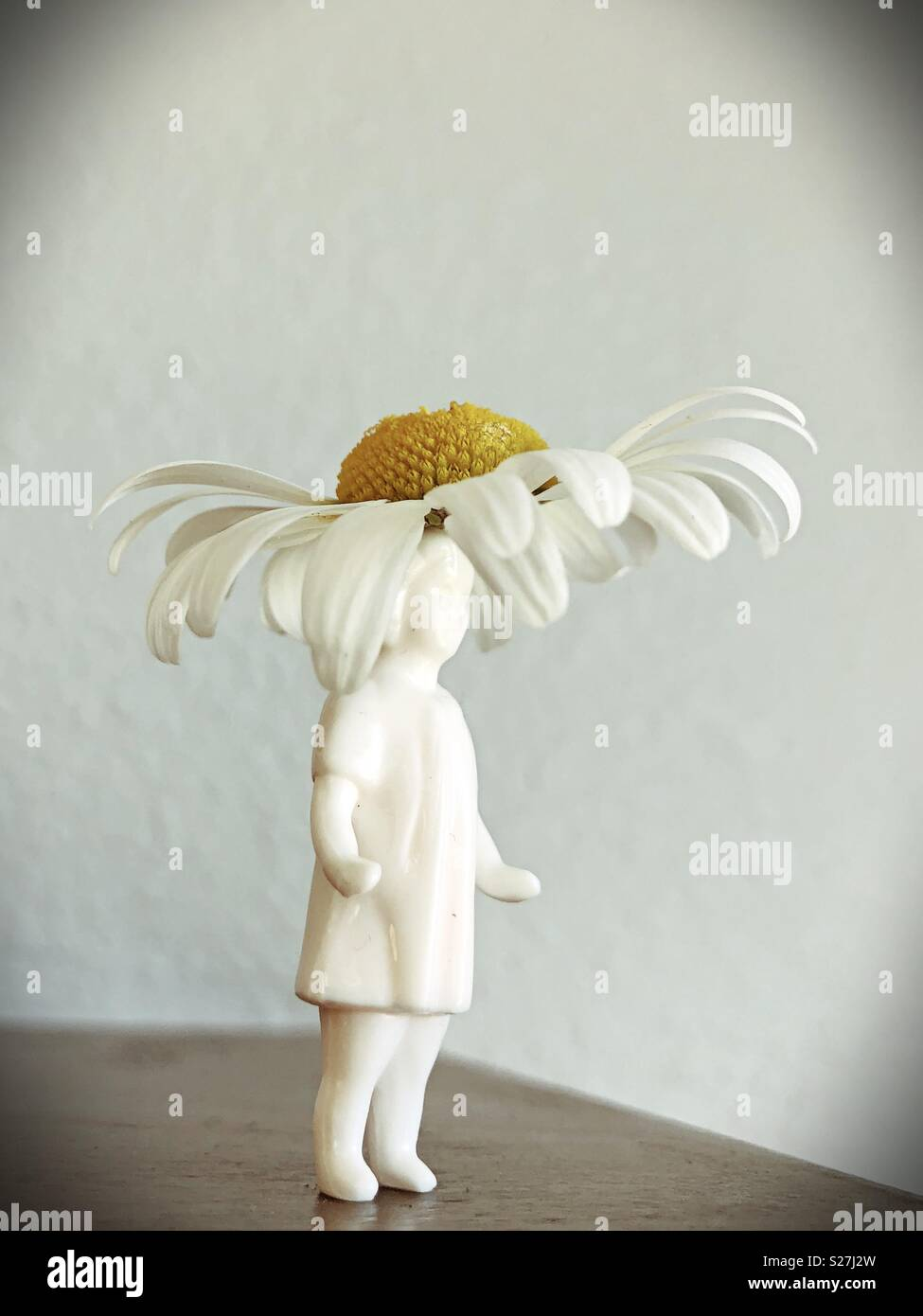 """A retro looking figurine of a girl with a real daisy """"hat"""". - Stock Image"""