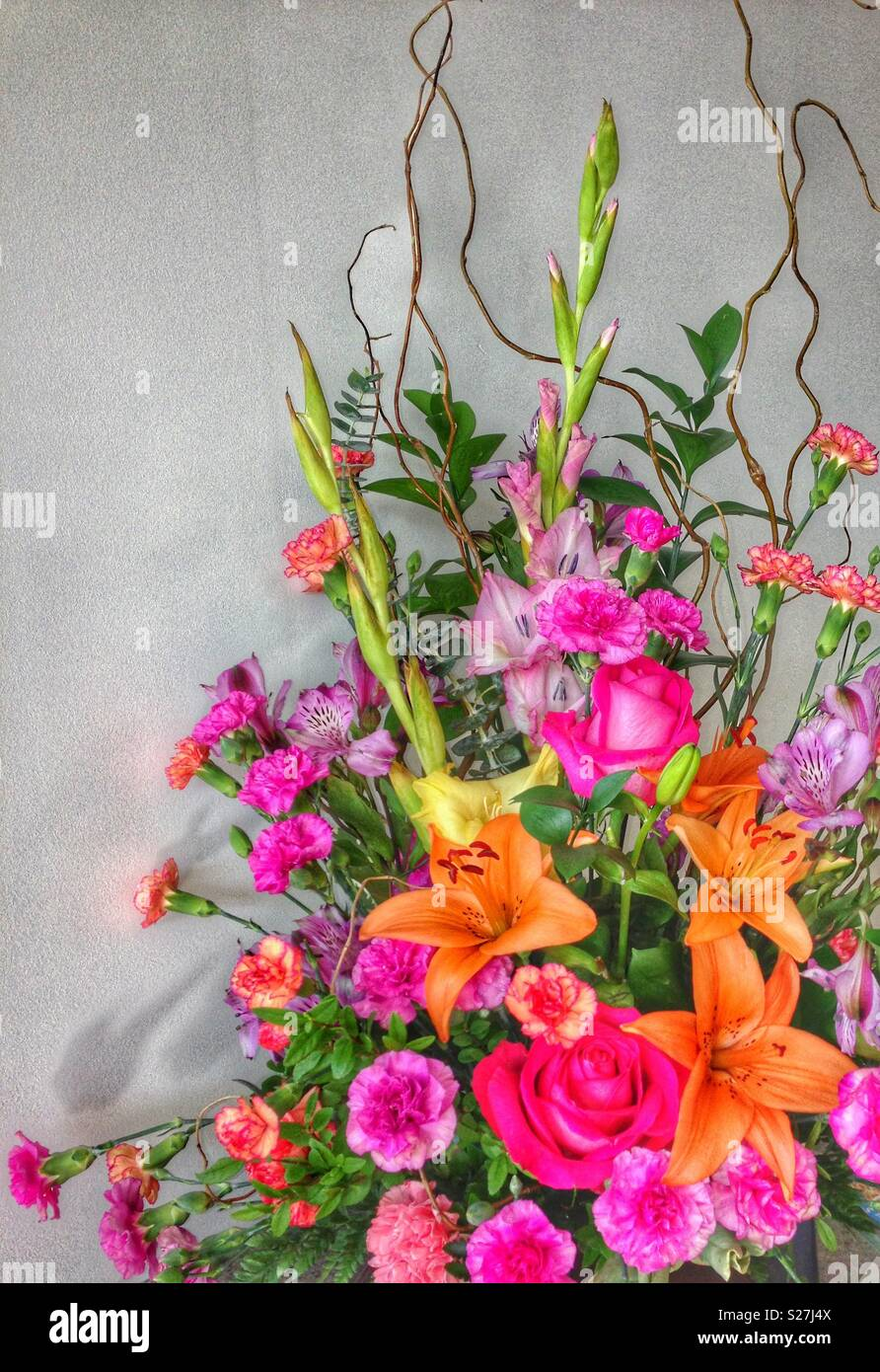 Bright colourful bouquet of tropical flowers like tiger liklies, carnations and roses. Orange, pink, green lush plant. Grey wall as background. - Stock Image