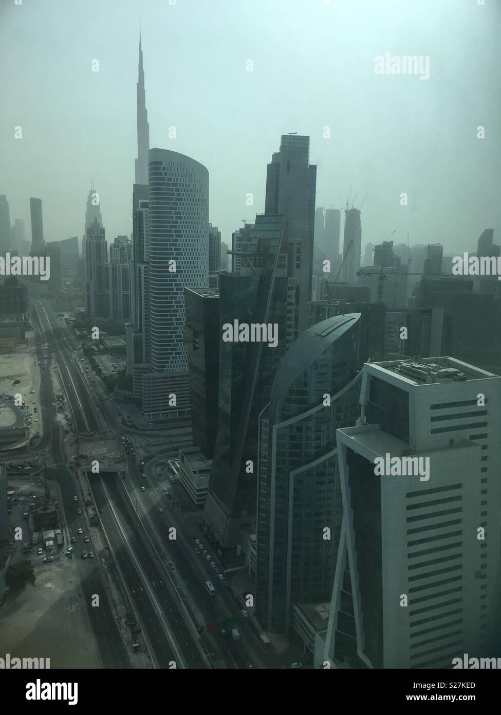 Sky scrapers in Dubai on a hazy day. Burj Khalifa in the background. - Stock Image