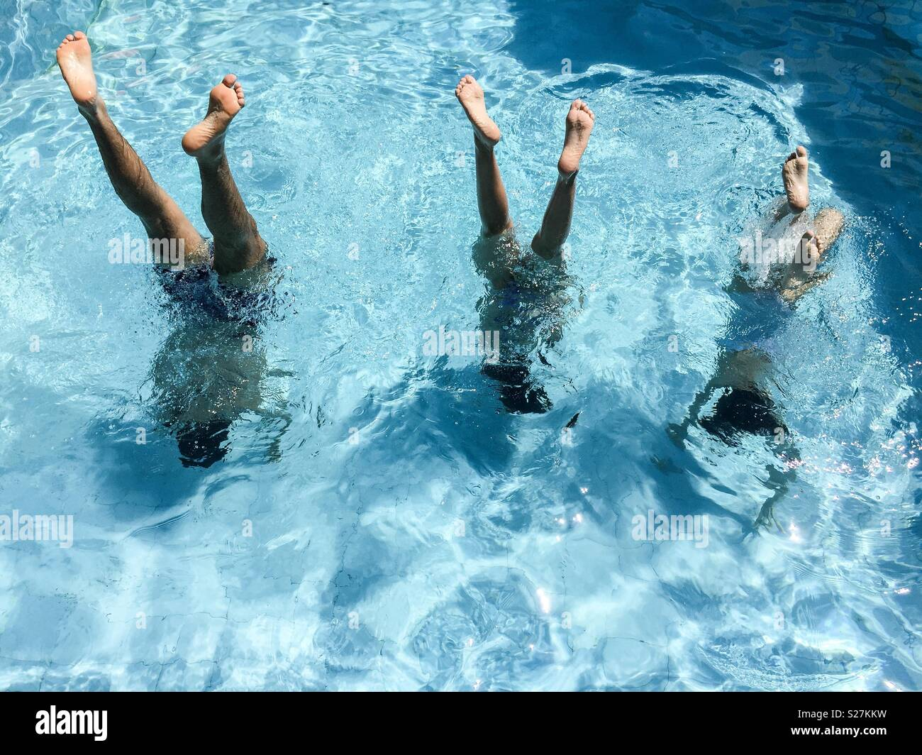 three teenagers doing balance in the pool - Stock Image