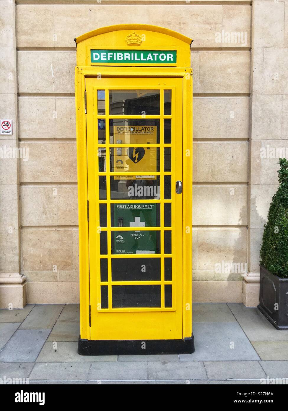 A former telephone booth has been repurposed to house a Defibrillator in Bath, England UK - Stock Image