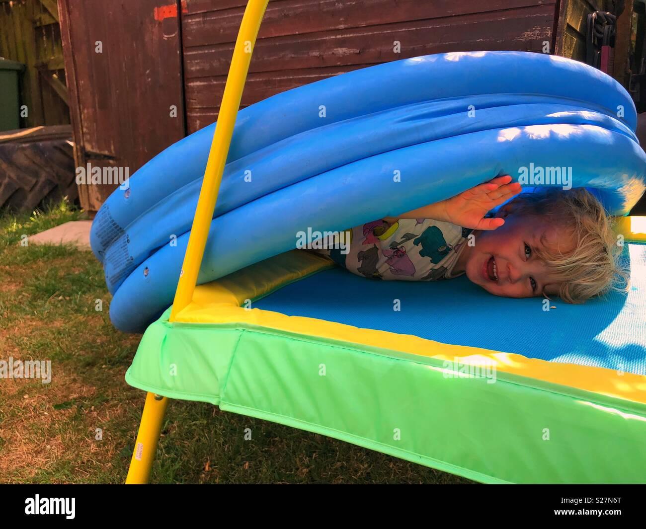 Toddler hiding in the garden - Stock Image
