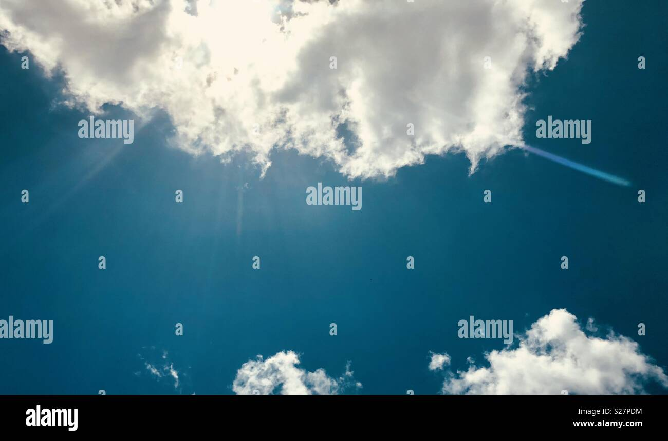 Partly cloudy sky with sunbeams and lens flare - Stock Image