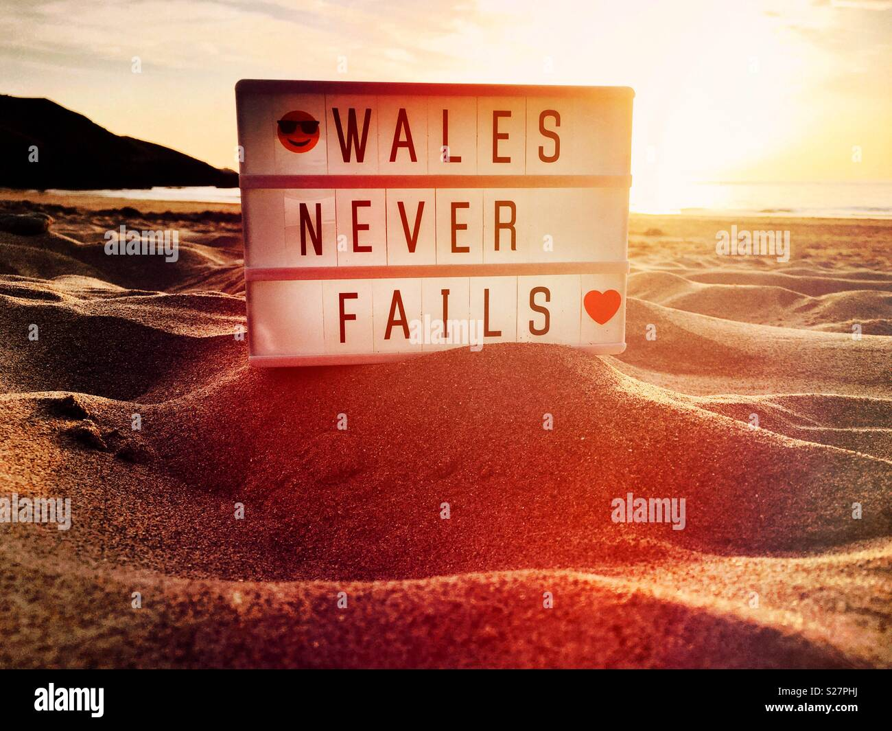 Wales never fails sign on a beach at sunset - Stock Image