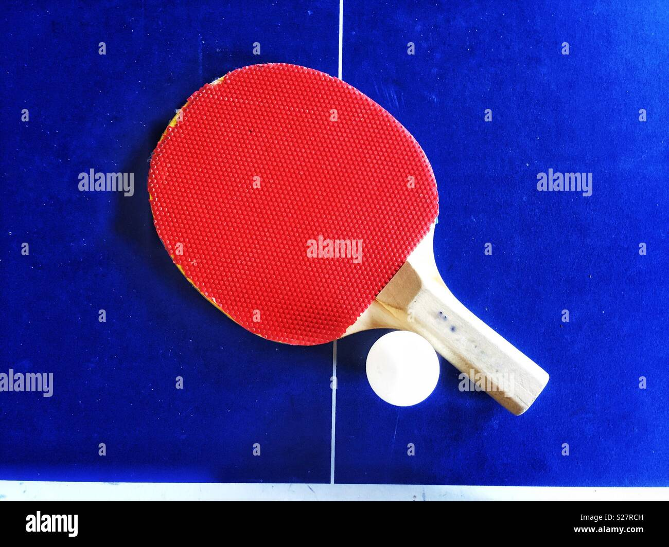 A red table tennis bat and ball on a bright blue table - Stock Image
