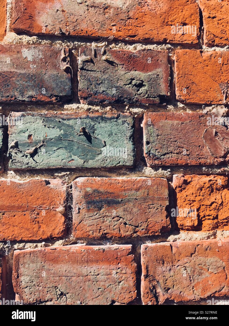 Victorian brickwork indicating its age with marks, damage and added paint - Stock Image