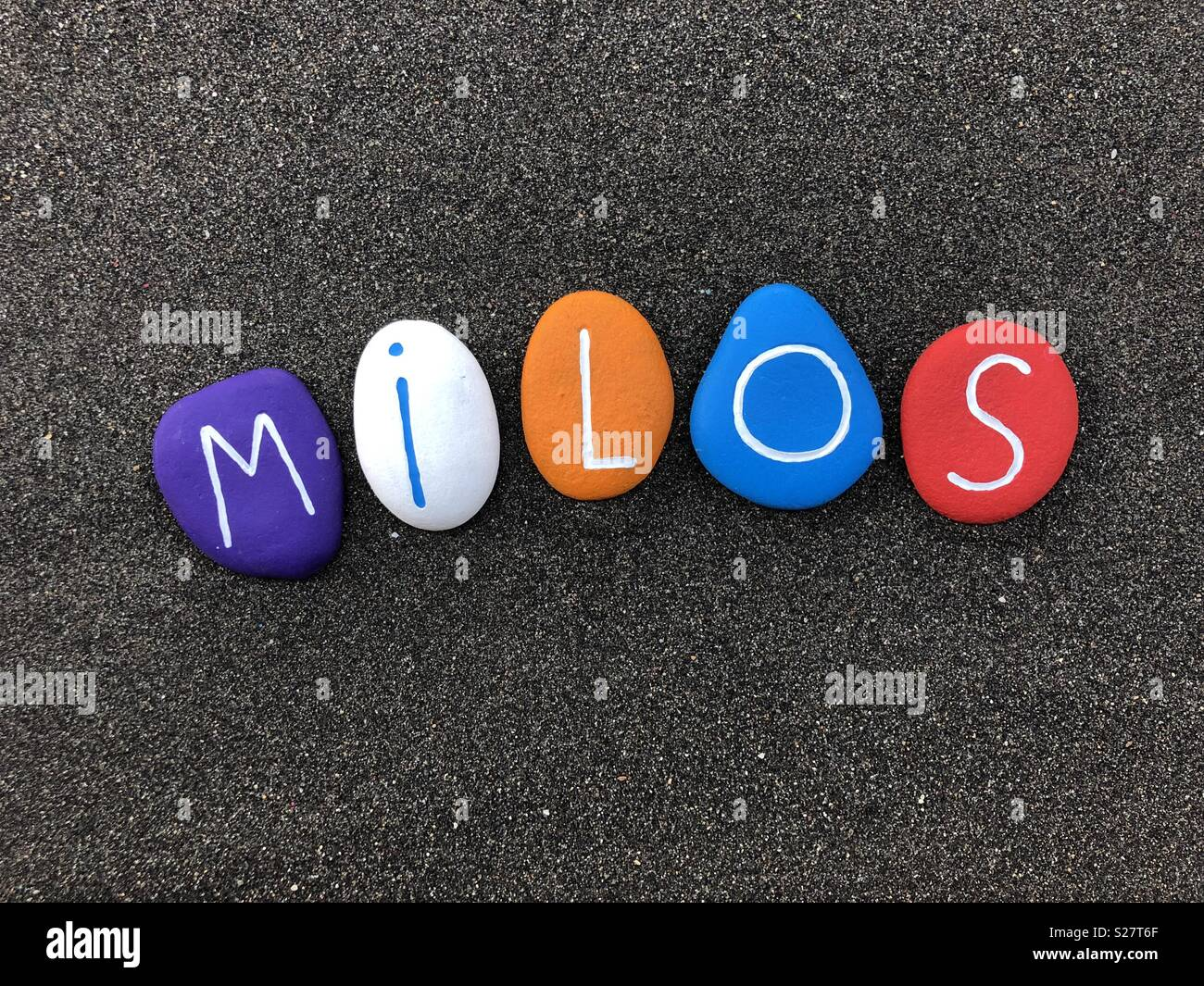 Milos, masculine given name with multi colored painted stone letters over black volcanic sand - Stock Image