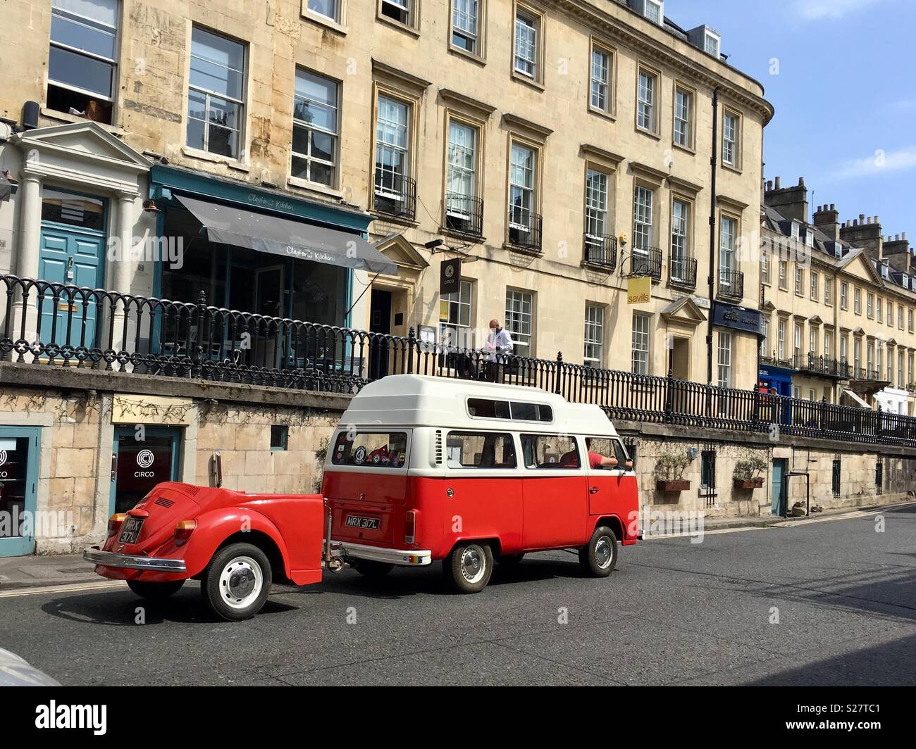 A Volkswagen camper van towing a VW bug on a street in Bath, England UK - Stock Image