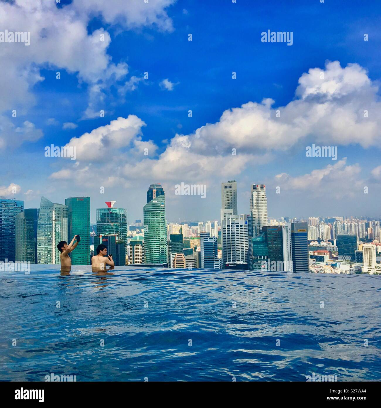 Marina Bay Sands Hotel pool in Singapore with two men taking photos and skyscrapers in background - Stock Image