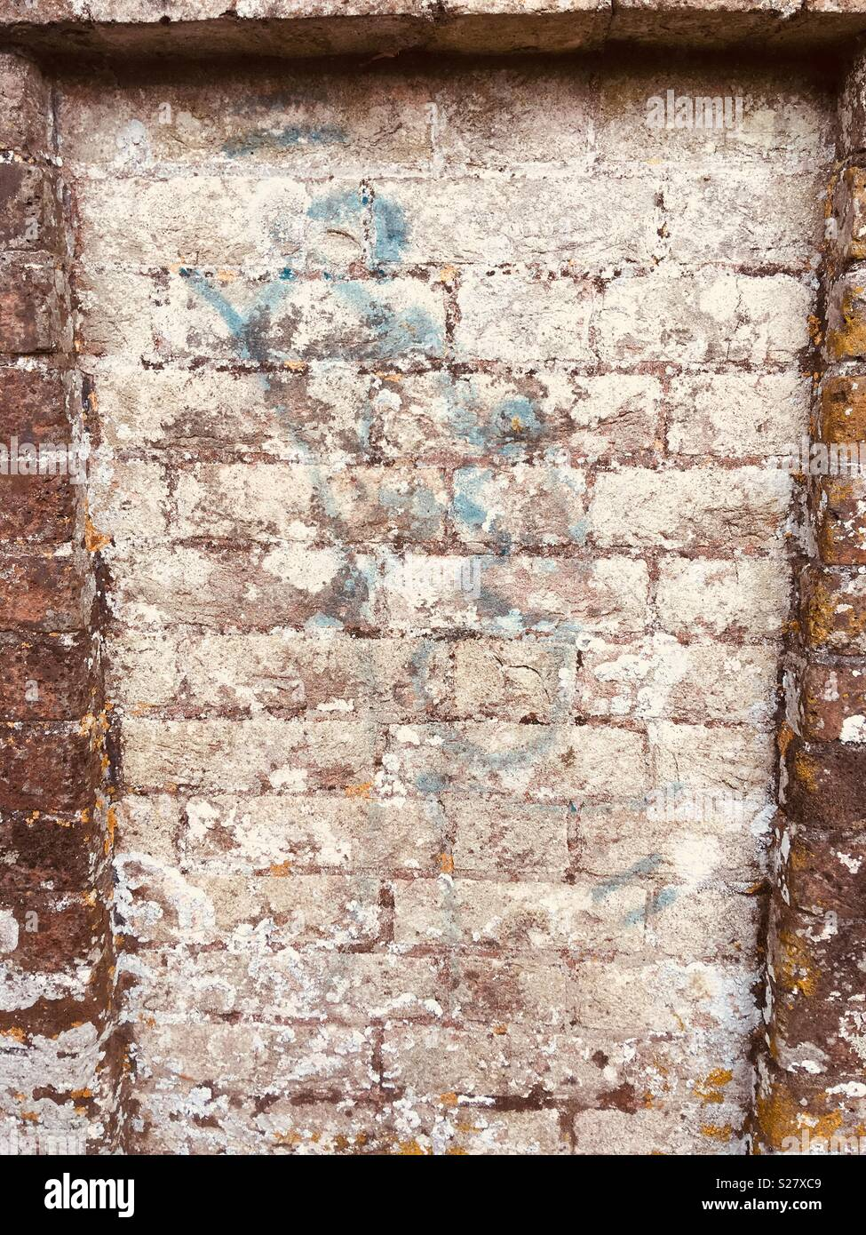 Painted blue marks on a brick wall - Stock Image