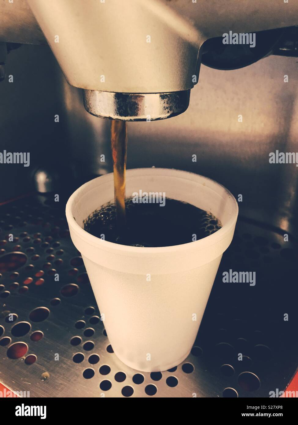 Coffee maker pouring a cup of coffee. - Stock Image