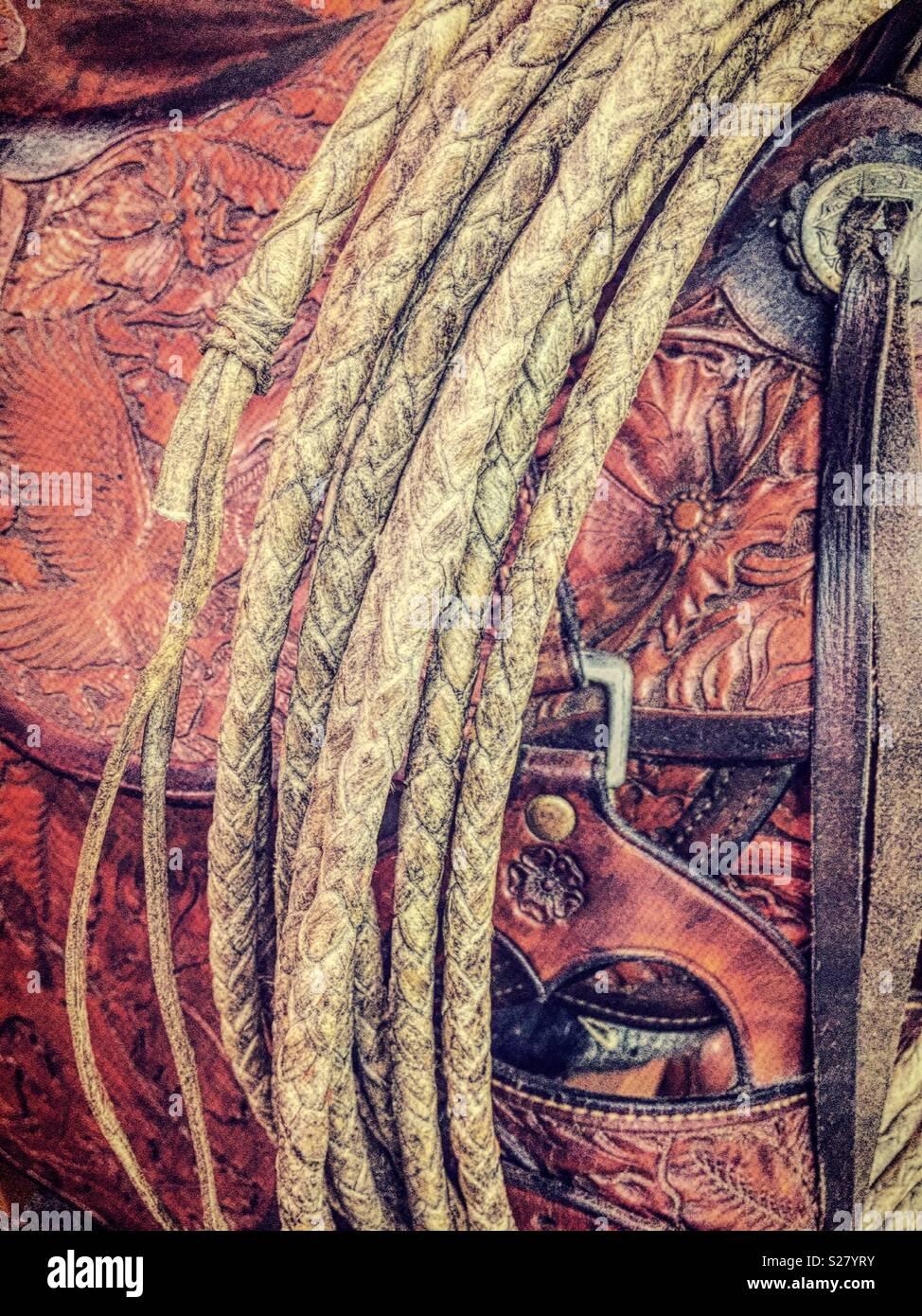Rawhide lasso is displayed with vintage leather western saddle, Montana, USA - Stock Image
