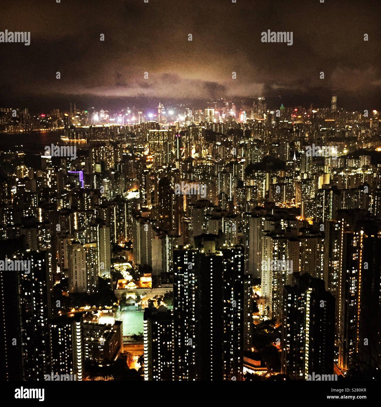 The bright lights of Hong Kong Island and Tsim Sha Tsui viewed across the high density urban landscape of the Kowloon Peninsula from the old Sha Tin Pass Road, Hong Kong (warm tone) - Stock Image