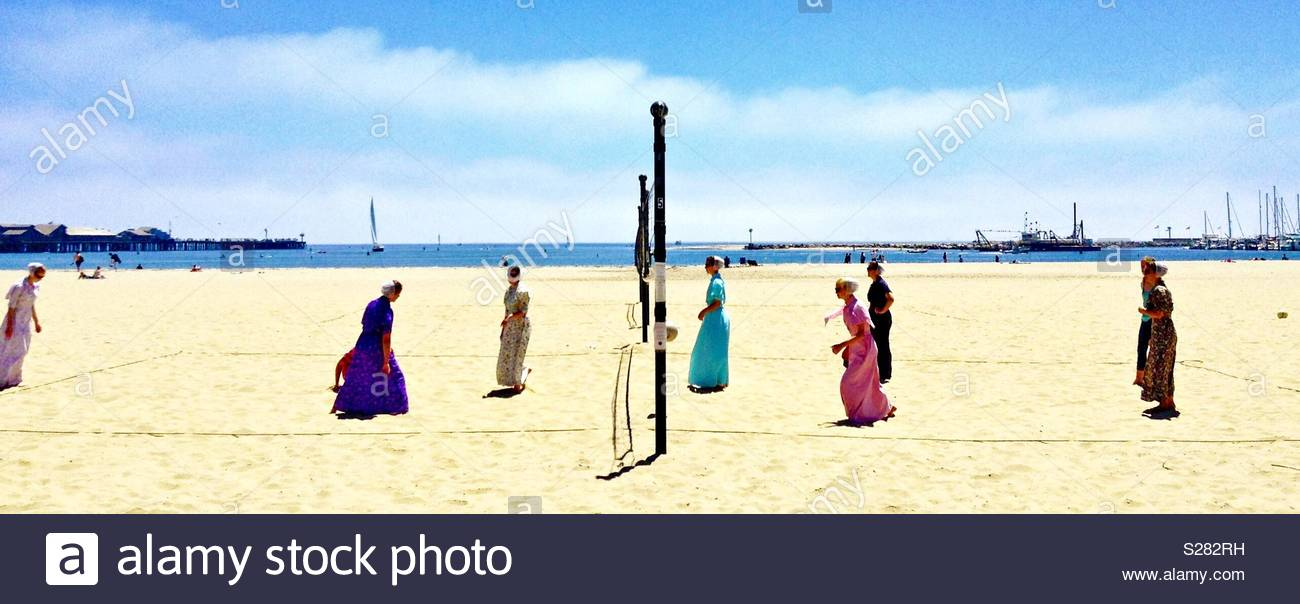 Women wearing skirts and bonnets, appearing in the dress of Mennonites play volleyball on the beach. - Stock Image