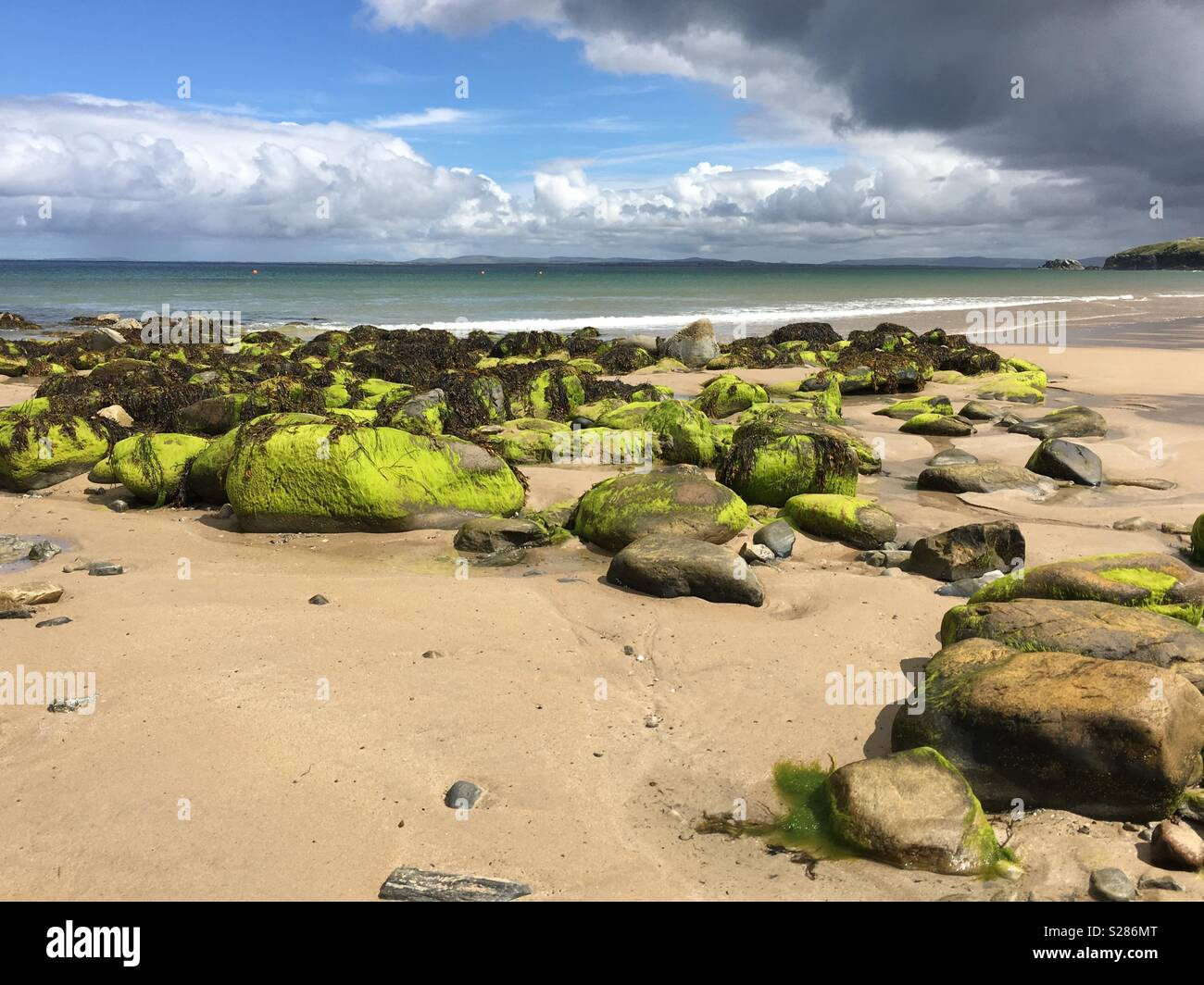A beach with green covered rocks and a blue sky with black clouds on Achill Island, County Mayo, Ireland - Stock Image