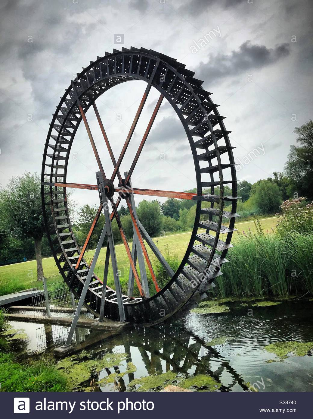 Water wheel spinning water bathed in green summertime colors. - Stock Image