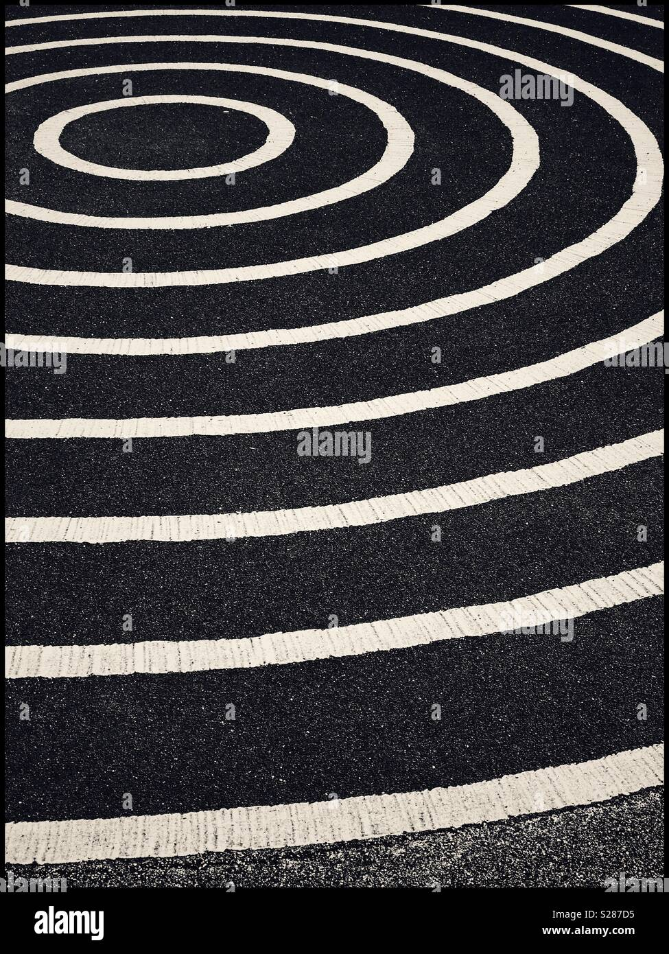 A graphic, monochrome image of concentric circles, painted onto a large area of tarmac (asphalt). An image with multiple potential uses. Photo Credit - © COLIN HOSKINS. - Stock Image