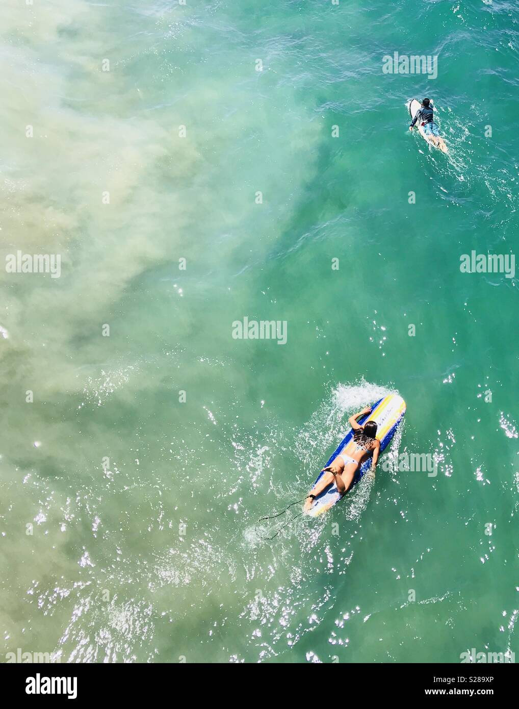 Surfers paddling out to surf. Manhattan Beach, California USA. - Stock Image