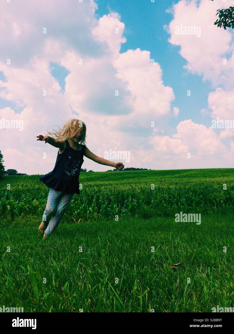 Young girl twirling in green field with blue sky above - Stock Image