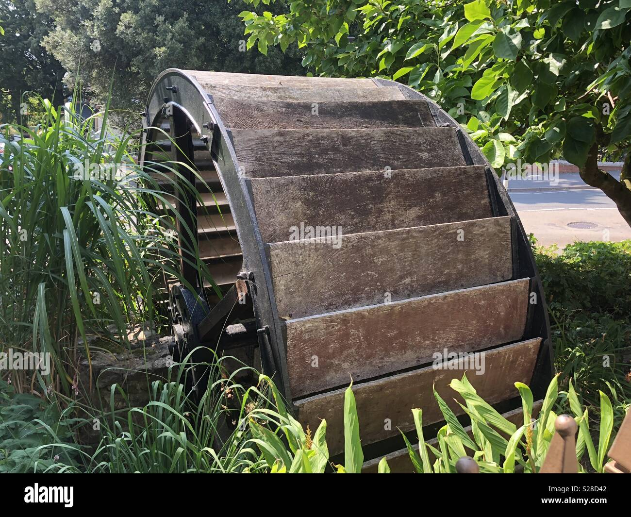 A rather striking water wheel, steeped in greenery, but alas no longer any water, but l contend quite beautiful an a natural treasure. Stock Photo