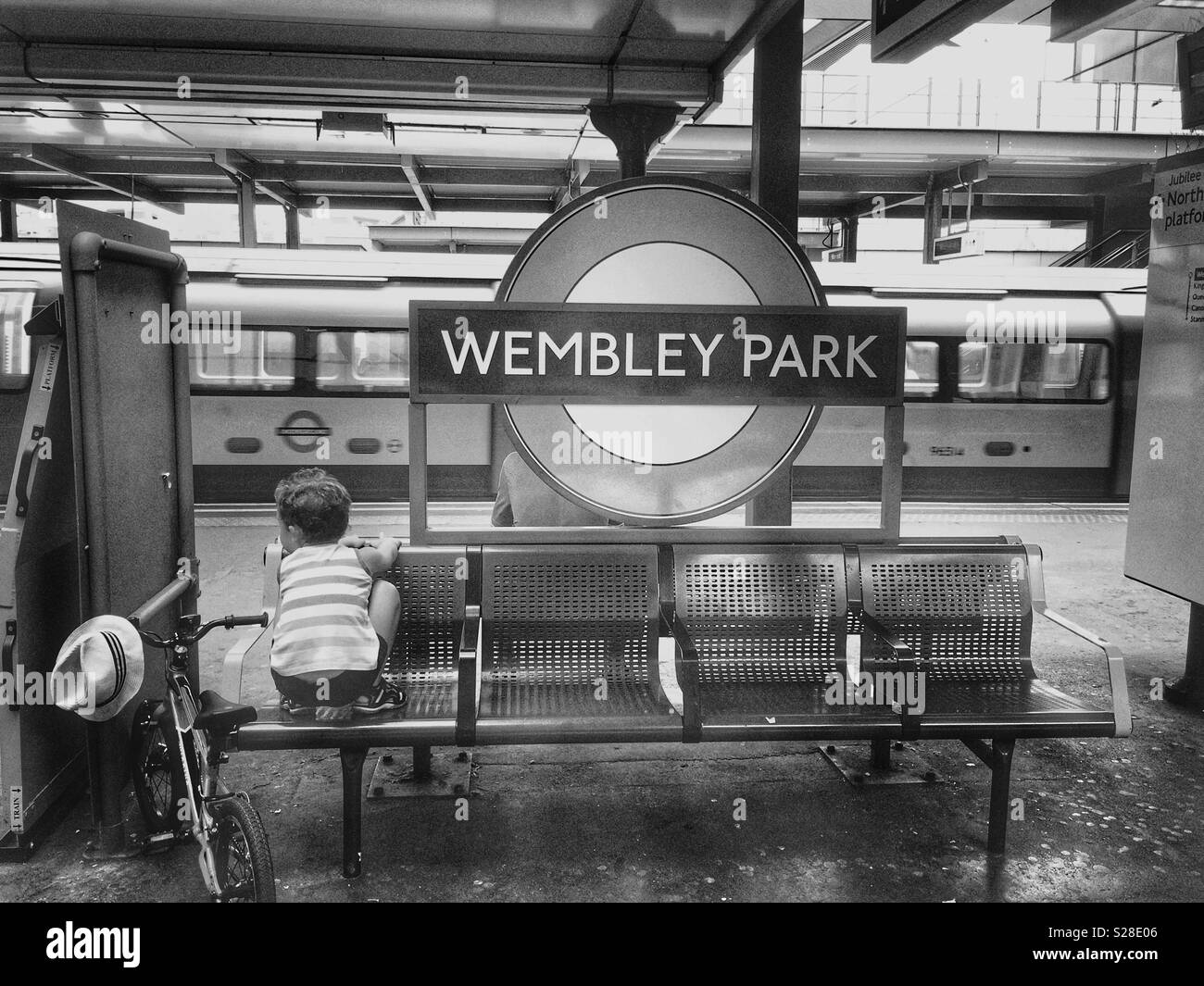 A boy with his bike looking at the trains at Wembley Park station, London - Stock Image