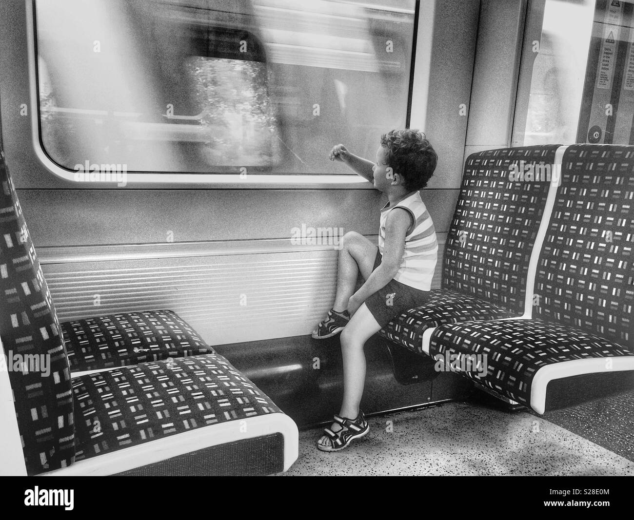 A boy looking through the window in the train - Stock Image