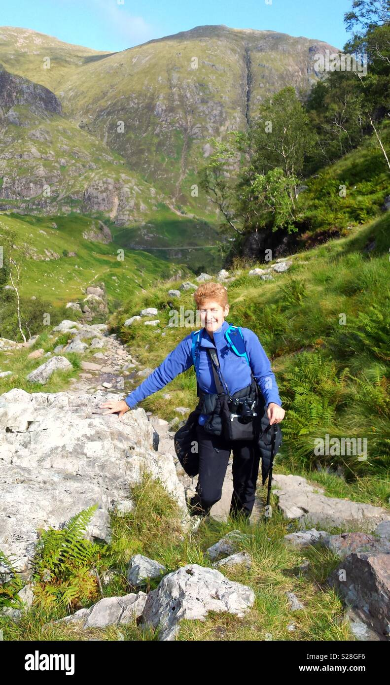 Mature female hiker climbing to the Lost Valley at Glencoe, Scotland, UK - Stock Image
