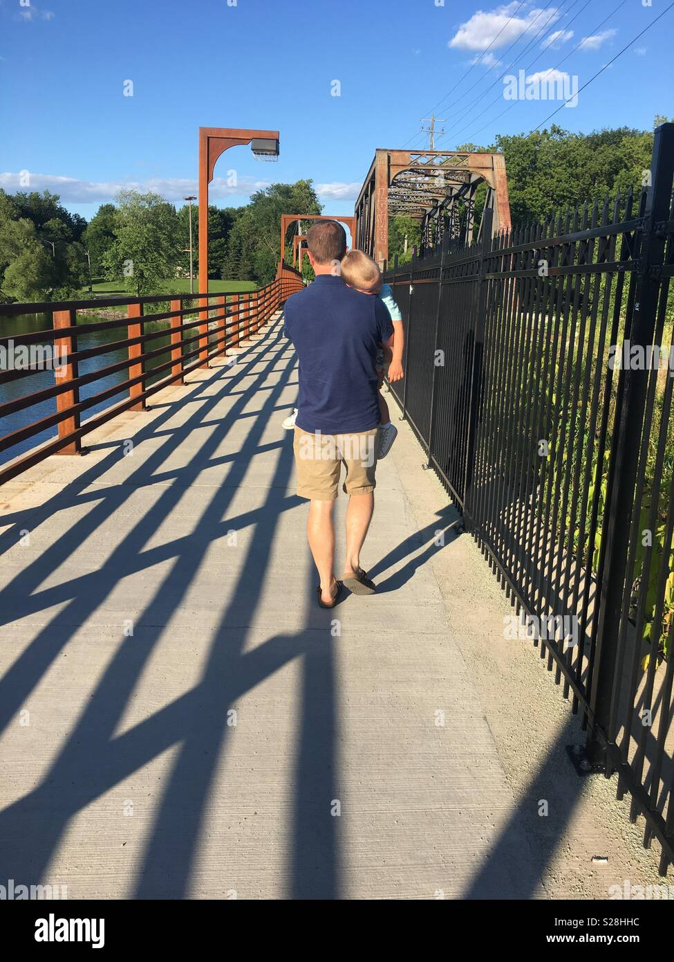 A dad carrying his son on a bridge - Stock Image