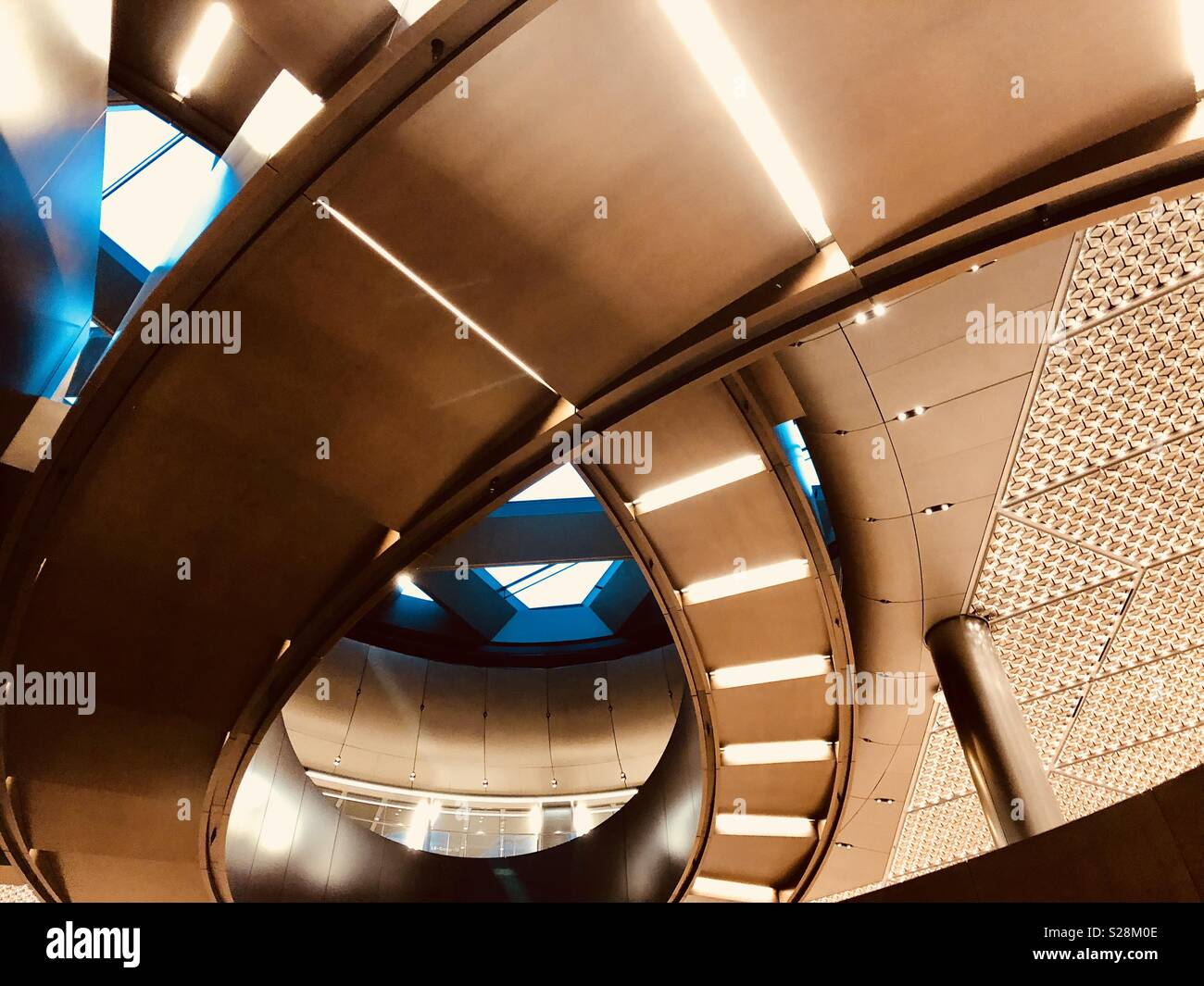 Contemporary modern spiral copper staircase rises up inside a business office building in London, U.K. - Stock Image