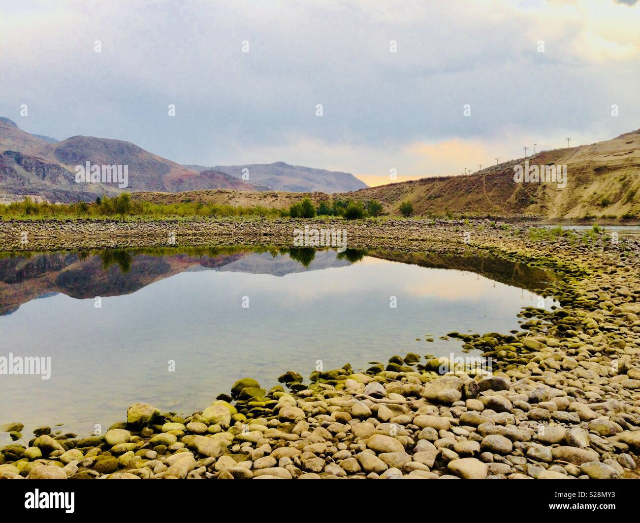 Stark landscape in Canada with pebbles and lake with hills in background - Stock Image