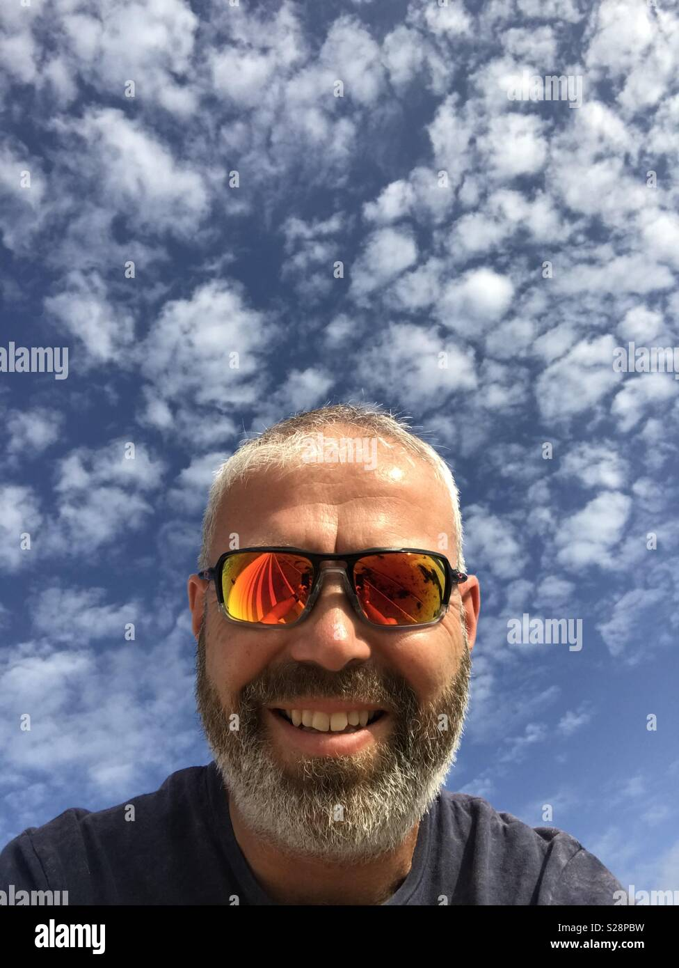 Smiling Bearded Man with Red Mirrored Shades on - Stock Image