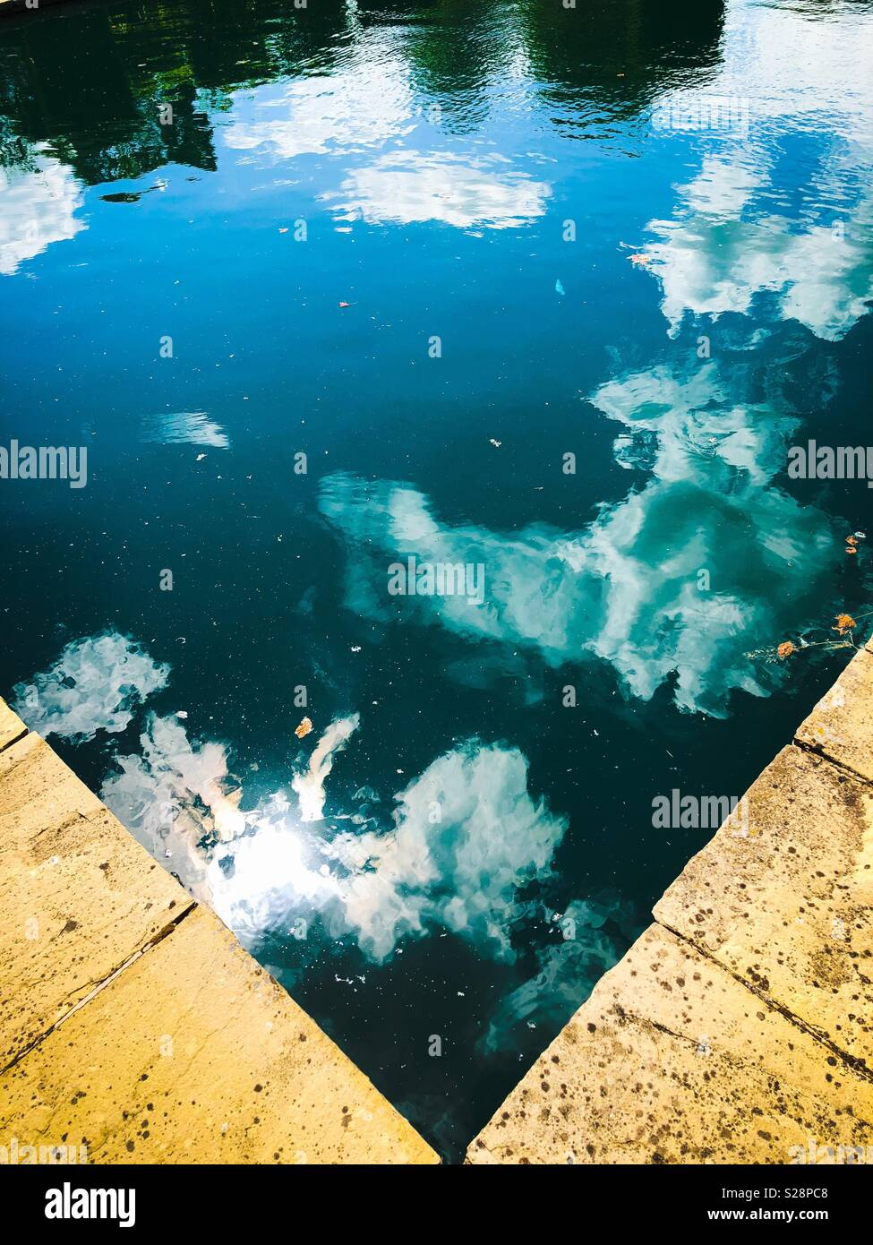 Clouds and blue sky reflections in a stone-edged pool - Stock Image
