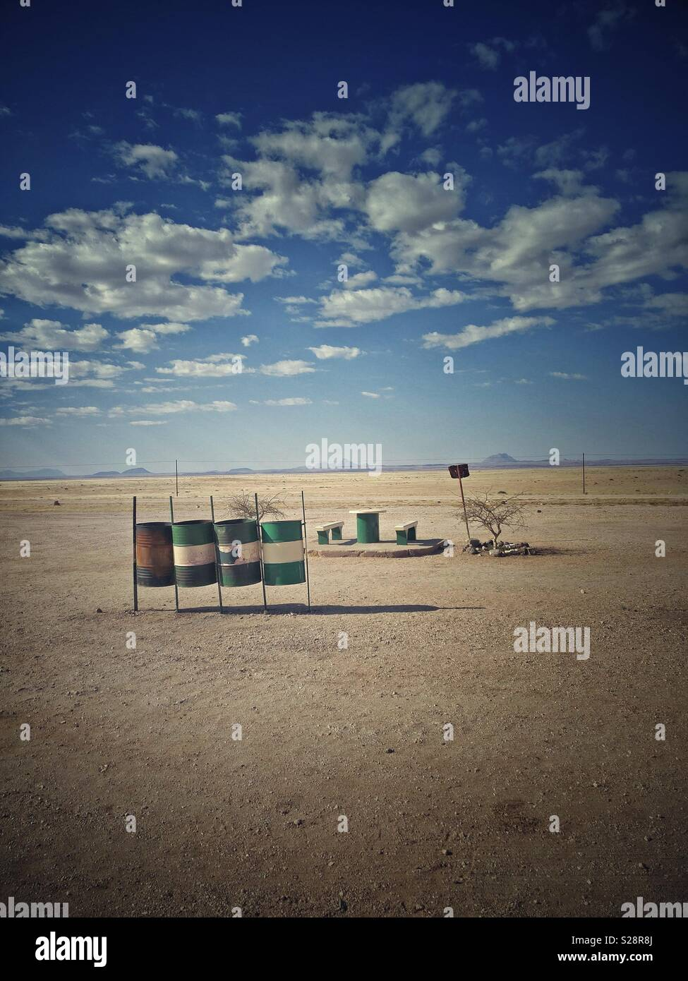 Roadside picnic area with oil drums for recycling bins, Namibia. Vintage look. Vertical portrait format with copyspace. Stock Photo