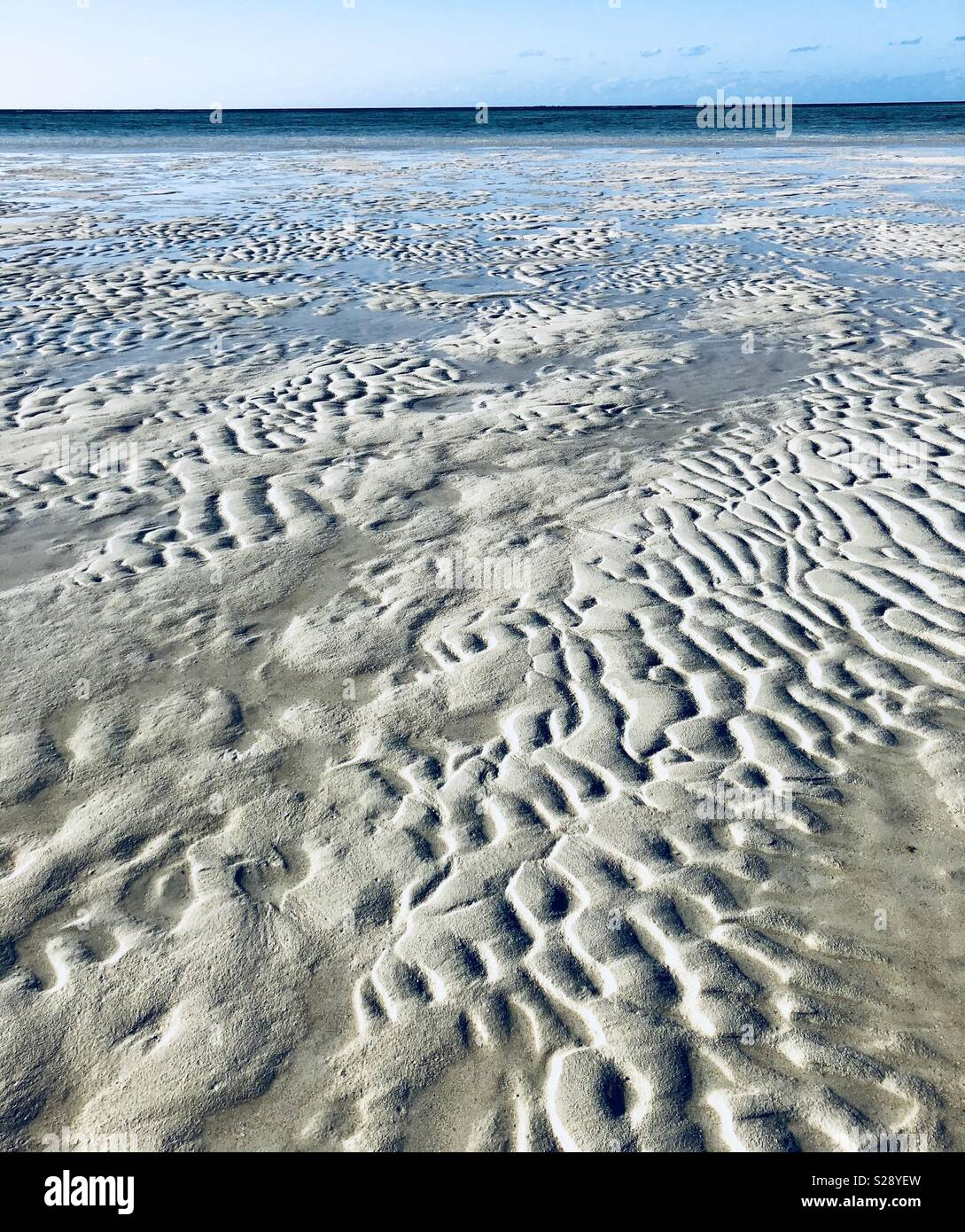 Wrinkles in sand at low tide - Stock Image