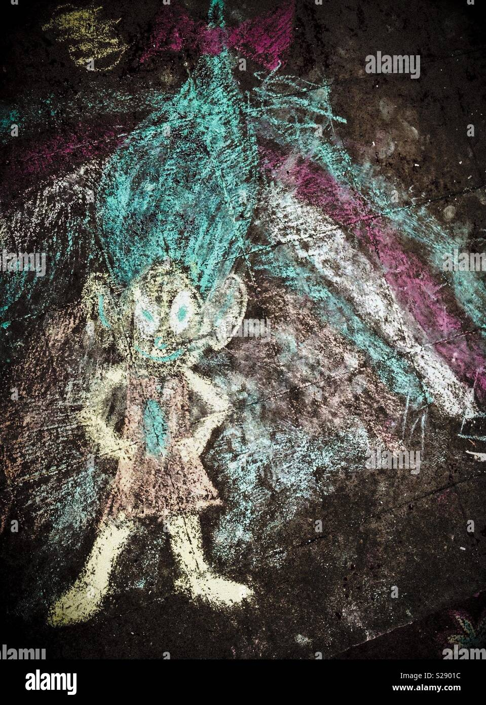 Darkened photo of chalk drawn troll and rainbow on porch cement - Stock Image