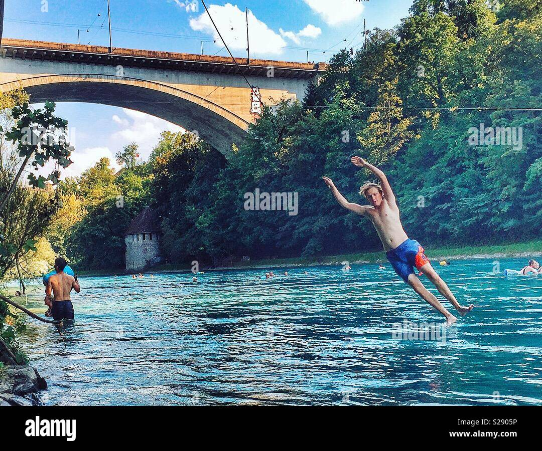 Young man entering the refreshing water of the Aare river, Bern, Switzerland - Stock Image