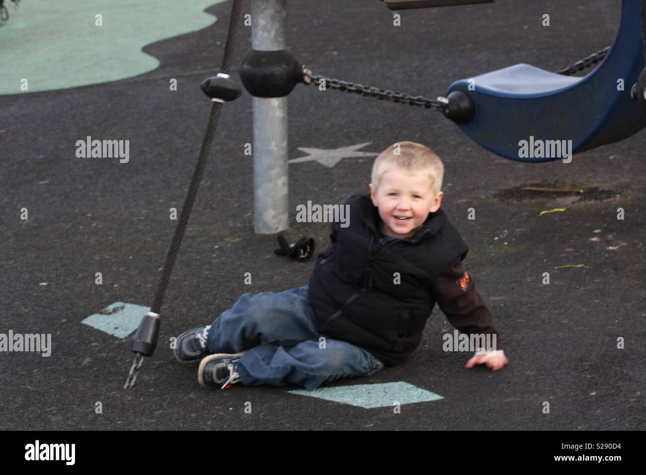 Little blonde haired boy sitting on floor in playground - Stock Image