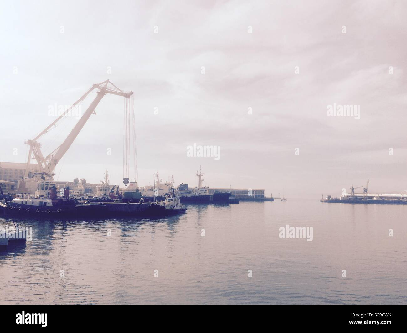 View onto the working harbour of Cape Town port in South Africa from the V&A Waterfront on a beautiful and calm Winter day - Stock Image