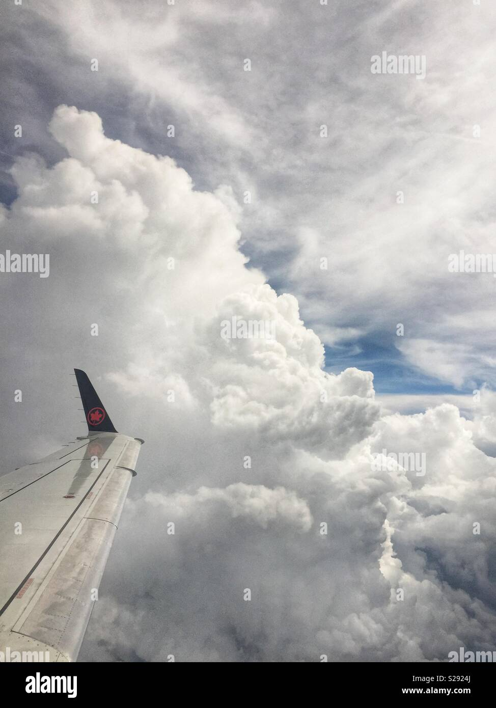 Air Canada Rouge flight from Newark, NY to Toronto navigates huge cumulus storm clouds during another hot and hazy afternoon on August 7, 2018. - Stock Image