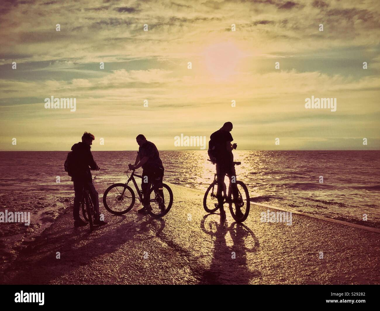 The silhouettes of three male cyclist friends as they relax near the edge of the sea at sunset. A Creative & atmospheric picture with multiple potential uses. Photo Credit - © COLIN HOSKINS. - Stock Image